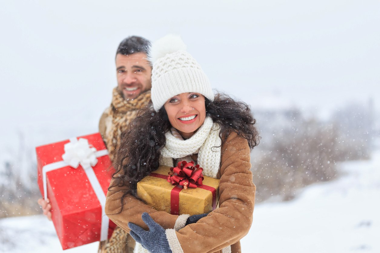 Young couple having fun with presents on snow mountain