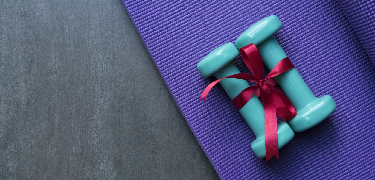 Fitness Gift of two green dumbbell with red gift bow on a yoga mat.