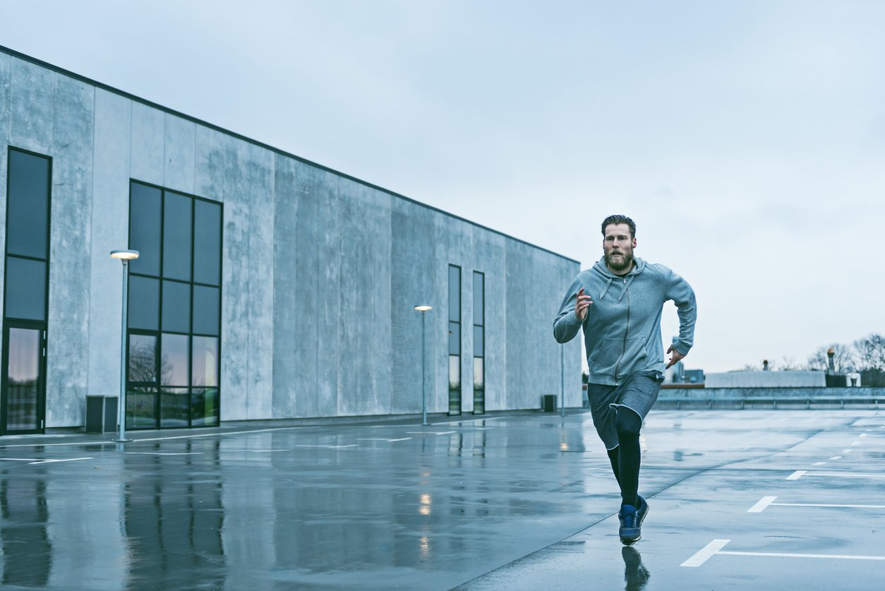 Man runs fast outside and the sky is grey and cold.
