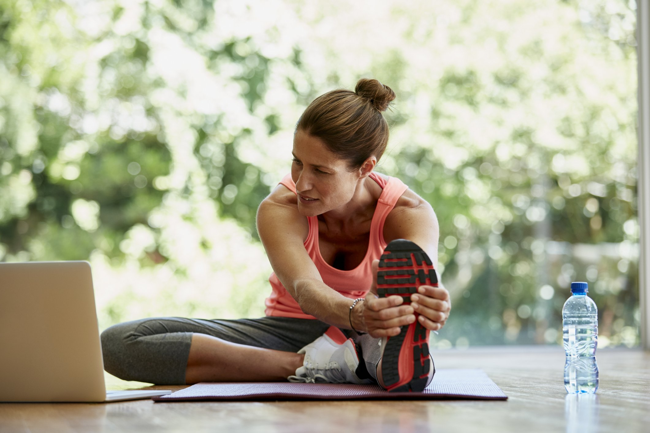 Full length of fit woman looking at laptop while doing stretching exercise at gym