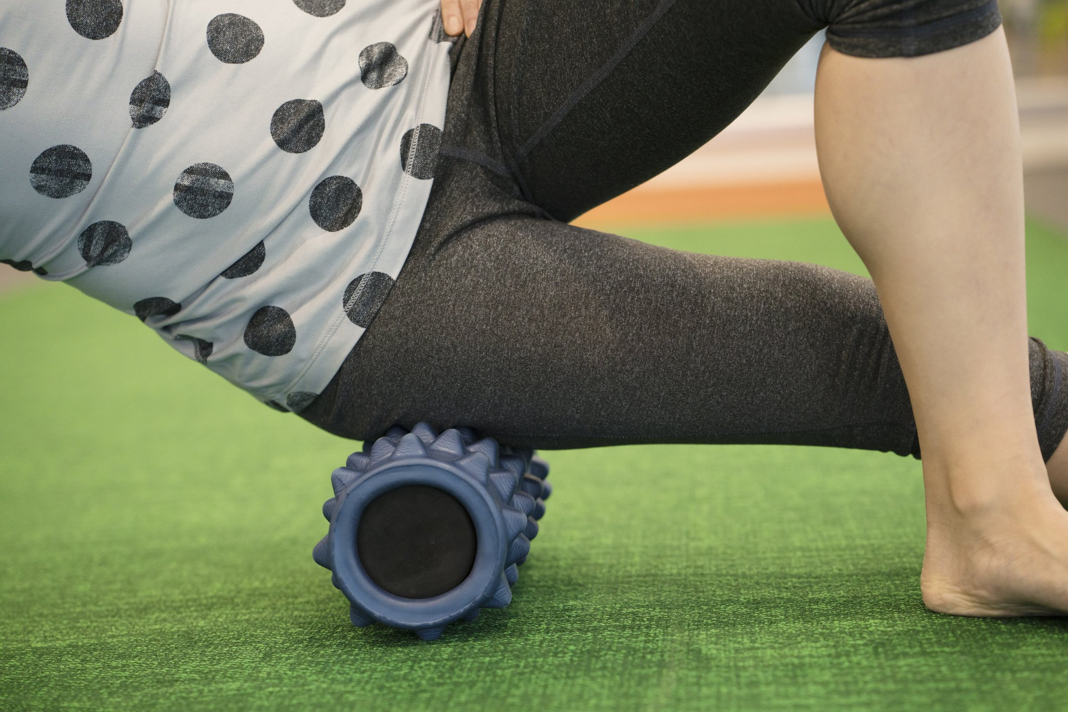 woman using a foam roll on her leg to release tension and help with muscle pain in the exercise class
